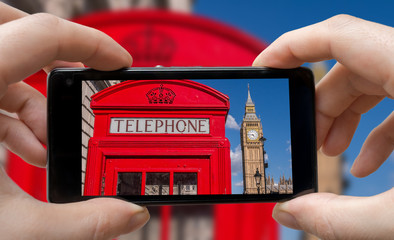 Tourist is taking photo of red phonebooth in London with smartphone.
