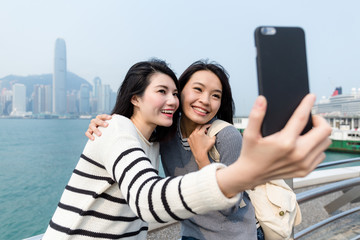 Two women taking self image with mobile phone