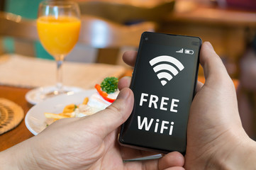 Man is using free wifi in restaurant with smartphone.