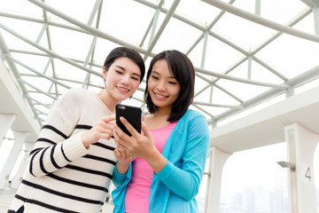Woman using mobile phone together