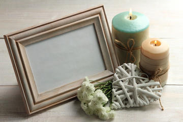 a bouquet of chrysanthemum with wooden frame for photo on wooden background with decorative white heart near the two candles