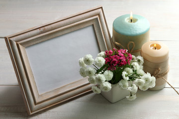 a bouquet of chrysanthemum with wooden frame for photo on wooden background with candles