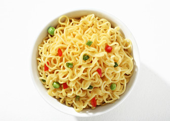Vermicelli with green peas and chopped bell pepper in white bowl on white background. Close up, top view, high resolution product.