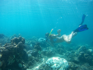 Underwater shot of the woman moving on the breath hold in the depth. Amed village, Bali, Indonesia