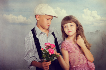 The boy gives a flower to the girl