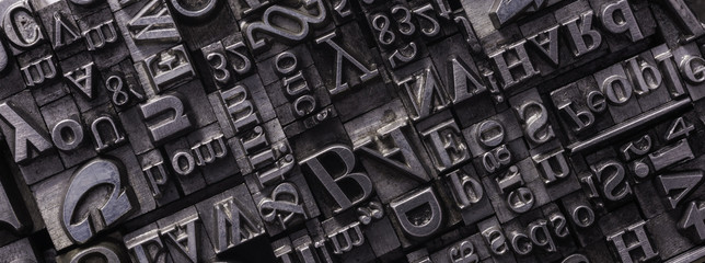 Fototapeta Metal Letterpress Types. A background from many historic typographical letters in black and white with white background.  obraz