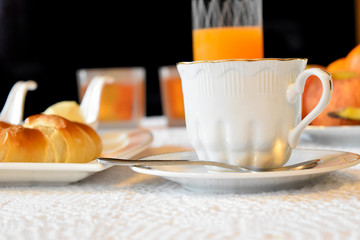 Breakfast with croissants, jam and butter, coffee, and fresh orange juice. A sunlit morning feast.