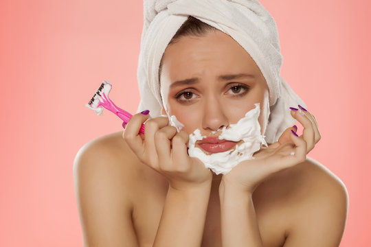 disappointed young woman with foam on the face and a razor in her hand