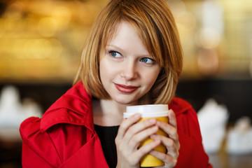 Woman drinking coffee indoors.