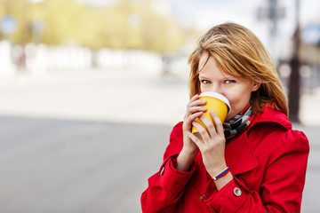 Young beautiful woman with to go coffee