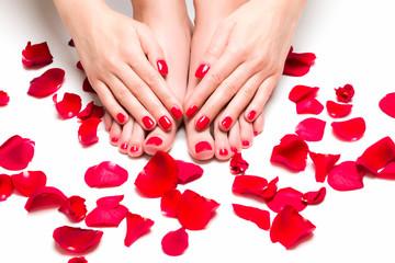 Stopy i dłonie otoczone płatkami róż