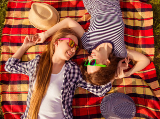 Top view of two happy girls in spectacles lying on plaid