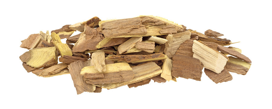 Small pile of mesquite smoking chips for barbecue isolated on a white background.