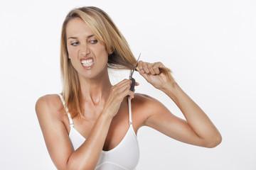 femme énervée qui coupe ses cheveux