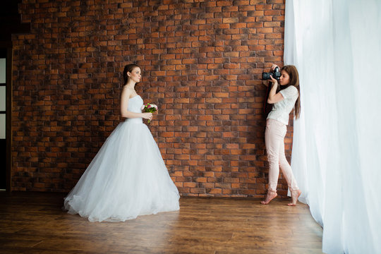 Young sexy woman photographer is taking pictures the bride in the studio