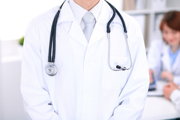 Close-up of a male doctor in a background of doctor and patient