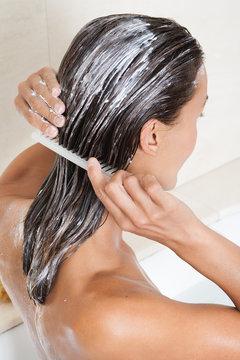 femme dans son bain appliquant une crème sur ses cheveux