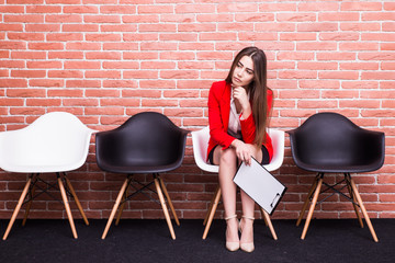 Confident young businesswoman holding paper while sitting on chair