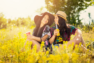 Two boho sisters drinking juice and coffee outdoors on sunny summer day
