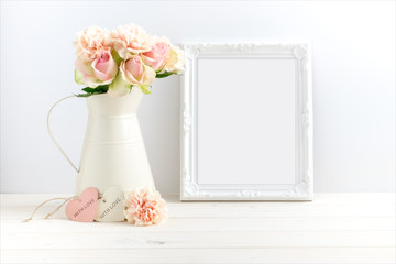 Mockup styled stock photograph of cream jug of flowers next to a white ornate frame. You can place your business promotion, blog title, quote, headline or image in the frame.
