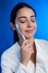 Dentista su sfondo azzurro con spazzolino da denti.