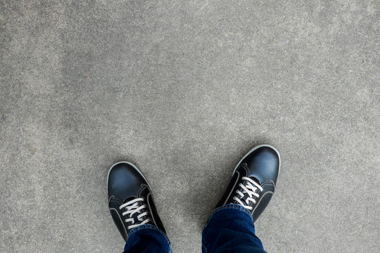 Black casual shoes standing on concrete floor
