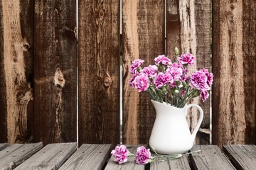 A white pitcher filled  with carnations sits on a rustic garden table.
