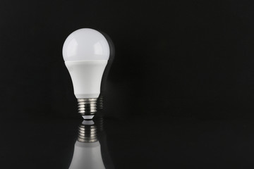 Led light bulb on dark background with reflection and  copy space on the right