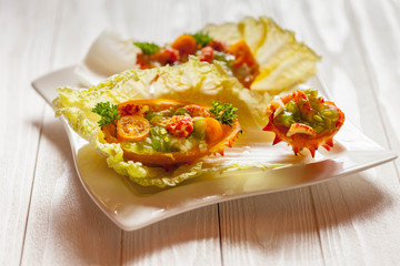 Exotic Shrimp salad served in n half a kiwano and leaves of the Chinese cabbage for summer party on wooden table, selective focus, copy space