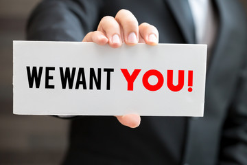 We want you, message on blackboard and hold by businessman