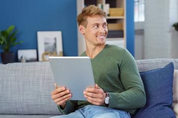 lächelnder mann auf dem sofa mit tablet in den händen