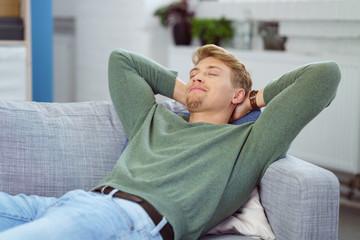 mann entspannt zuhause auf dem sofa mit armen hinter dem kopf