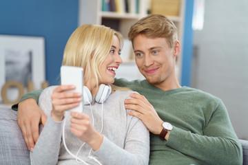lachende frau zeigt ihrem freund etwas am smartphone