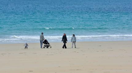 Une famille avec une poussette se promène sur la plage de Trestraou à Perros-Guirec en Bretagne