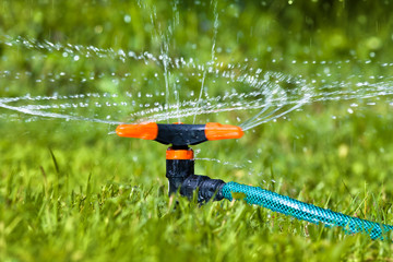 garden sprinkler spraying water over grass