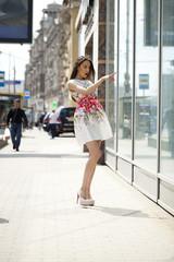 Young beautiful brunette woman in white flowers dress walking on