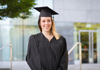 Portrait of female college student in graduation cap and gown on