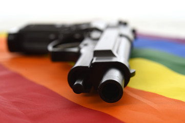 still life with close up gun resting on gay parade flag representing sexual discrimination and intolerance