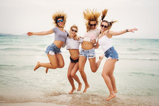 Young attractive teenagers jumping at beach. It's the beginning of spring break.