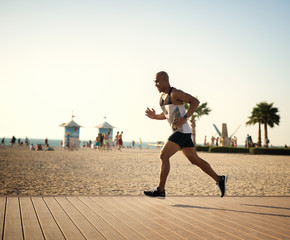 Handsome man at the beach, running.
