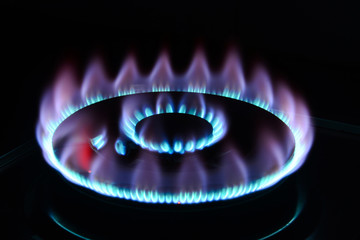 The blue flame of a cooker burner in the dark