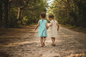 Two little girls on a forest road