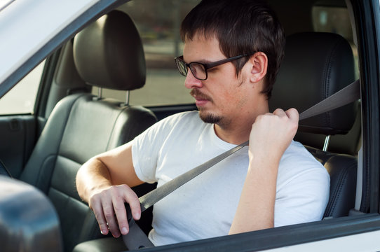 Male european driver is using seat belt in a car