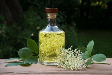 Homemade elderflower drink in a glass bottle on a wooden table in the garden