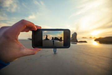 A man uses his smartphone to take a picture of his wife on Bandon Beach, Oregon.