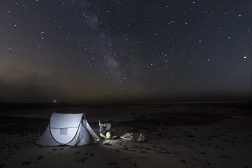 Surfer watching the stars camping on the beach at night