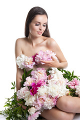 beautiful girl with flowers peonies. Portrait of a young woman with a dress of flowers.