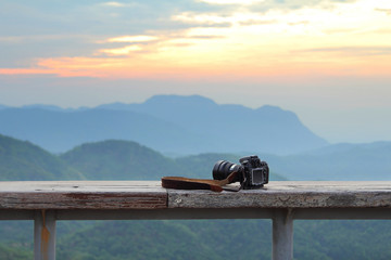 Dslr photo camera is placed on a wooden terrace with a beautiful background of sunrise.