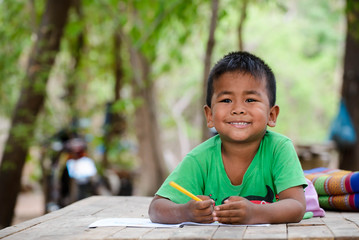 Asian child (poor kids) study at old home.Asia boy learning to drawing,painting with color pencil. Poverty child,smile,lying on dirty wooden table and writing on books.Poor Quality Education Concept. Wall mural