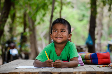 Asian child (poor kids) study at old home.Asia boy learning to drawing,painting with color pencil. Homeless child,smile,lying on dirty wooden table and writing on books.Poor Quality Education Concept. Wall mural